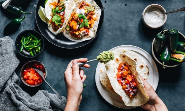 Assembling vegan tacos full of bright colored fillings on a dark background
